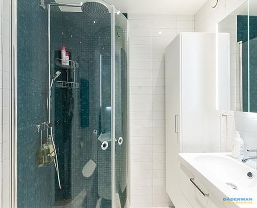 Badrum med blå mosaik och vitt kakel