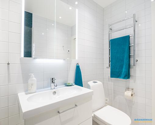 Badrum med blå mosaik och vitt kakel i Vallentuna