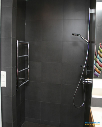 Svart badrum med varma trädetaljer
