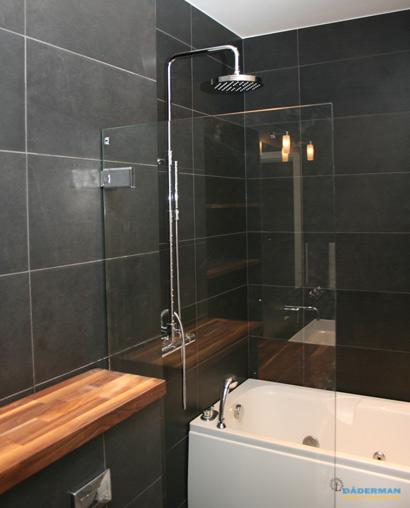 Badrum med belysta nischer i svart mosaik