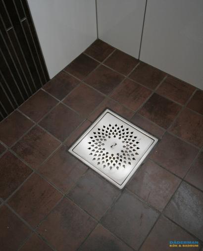Badrum med golv i brunt klinker