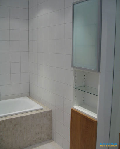 Badrum med vitt kakel och beige klinker