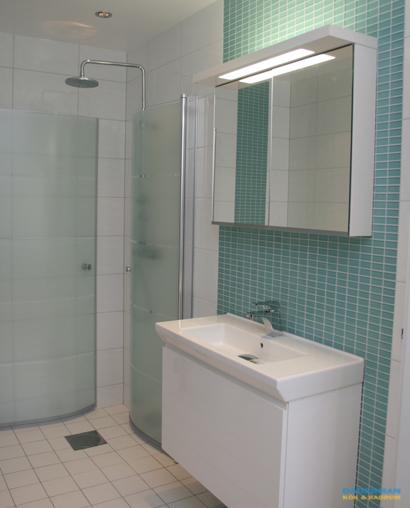 Badrum med vitt kakel och blå glasmosaik