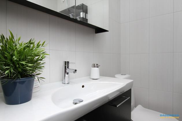 Badrum med vitt kakel och grå klinker